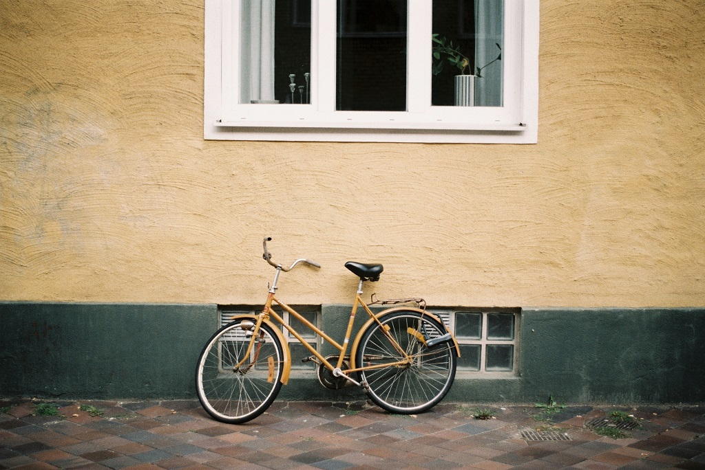 Gold bike propped up against a wall. Porch shares some important tips and tricks on what to consider when thinking about bicycle storage